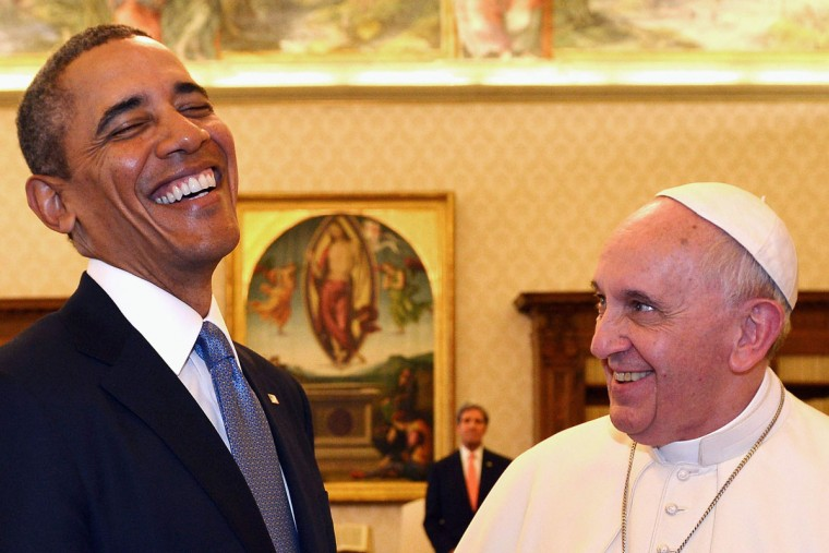 Pope Francis (R) and U.S. President Barack Obama react as they exchange gifts during a private audience at the Vatican City March 27, 2014. (Gabriel Bouys/Reuters)