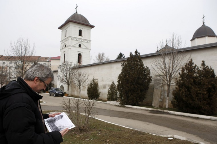"""Photo enthusiast Cezar Popescu looks at an image of the Sfintii Voievozi monastery taken from the """"Costica Acsinte picture archive"""" in Slobozia February 21, 2014. Popescu is digitising the work of Romanian photographer Costica Acsinte, who was an army photographer during the First World War and later had a small studio in the southern Romanian city of Slobozia before his death in 1984. Acsinte's photographs, shot on glass plates, celluloid plates and film, document more than half a century of life in Romania. However, they were kept in poor conditions and had already deteriorated before many of them came into the possession of the Ialomita County Museum, where they are now. Popescu is working as a volunteer to help preserve the images by scanning them and making them publicly available online. Picture taken February 21, 2014. (REUTERS/Bogdan Cristel)"""
