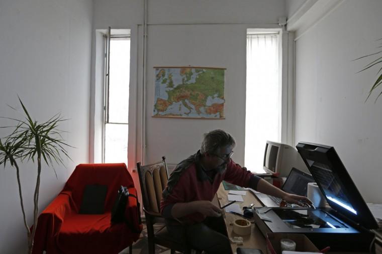"Photo enthusiast Cezar Popescu scans a negative from the ""Costica Acsinte picture archive"" at Ialomita county museum in Slobozia February 21, 2014. (REUTERS/Bogdan Cristel)"