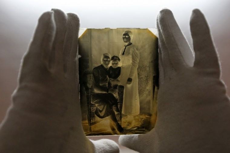 """A museographer holds a glass plate negative from the """"Costica Acsinte picture archive"""" at Ialomita county museum in Slobozia February 18, 2014. (REUTERS/Bogdan Cristel)"""