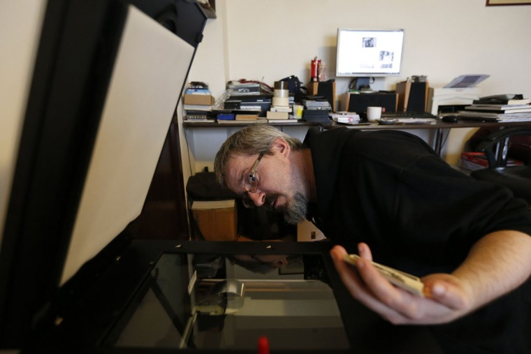 """Photo enthusiast Cezar Popescu cleans the scanner before digitalizing negatives from the """"Costica Acsinte picture archive"""" in Slobozia February 18, 2014. (REUTERS/Bogdan Cristel)"""