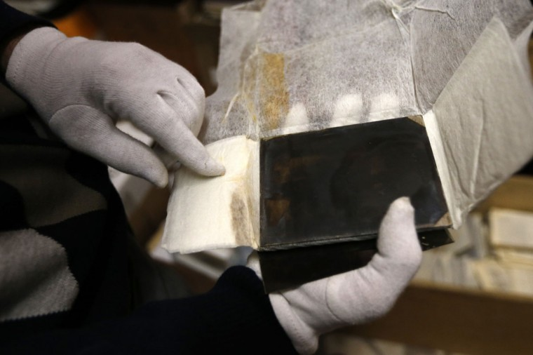 "A museographer holds glass plate negatives from the ""Costica Acsinte picture archive"" at Ialomita county museum in Slobozia February 18, 2014. (REUTERS/Bogdan Cristel)"