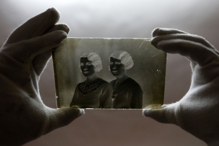 "A museographer holds a glass plate negative from the ""Costica Acsinte picture archive"" at Ialomita county museum in Slobozia February 18, 2014. (REUTERS/Bogdan Cristel)"