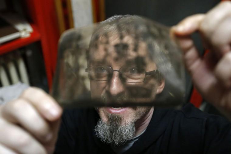"Photo enthusiast Cezar Popescu looks at a negative from the ""Costica Acsinte picture archive"" at Ialomita county museum in Slobozia February 18, 2014. (REUTERS/Bogdan Cristel)"