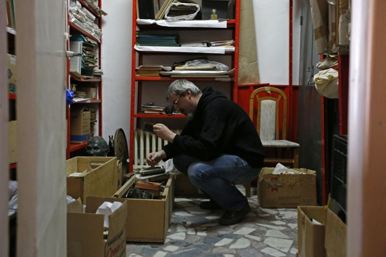 """Photo enthusiast Cezar Popescu looks at negatives from the """"Costica Acsinte picture archive"""" at Ialomita county museum in Slobozia February 18, 2014.(REUTERS/Bogdan Cristel)"""
