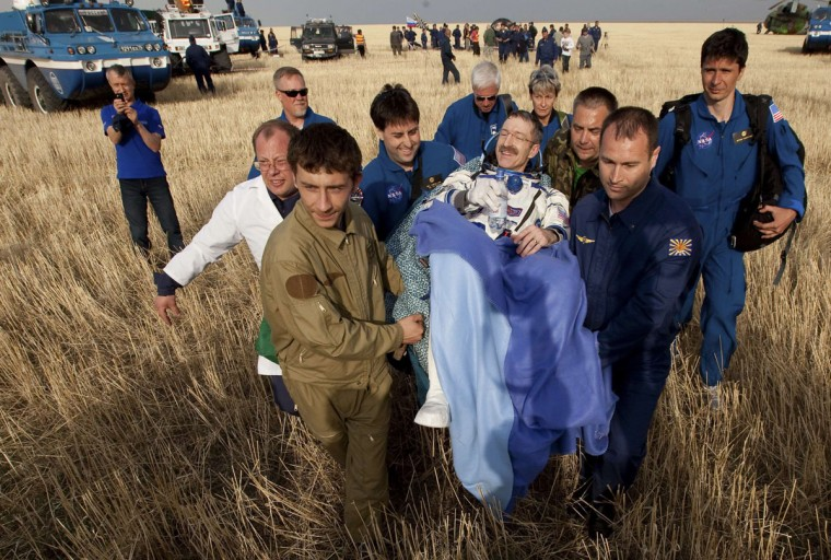 Ground personnel carry International Space Station (ISS) crew member U.S. astronaut Daniel Burbank shortly after landing in Kazakhstan, some 55 miles northeast of Arkalyk, on April 27, 2012. (REUTERS/Sergei Remezov)