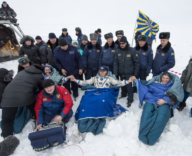 Former ISS commander Oleg Kotov (C) and flight engineers Sergei Ryazansky (L) and Michael Hopkins from NASA sit in chairs outside the Soyuz TMA-10M capsule shortly after they landed in a remote area southeast of the town of Zhezkazgan in central Kazakhstan, March 11, 2014. An American astronaut and two Russians who carried a Sochi Olympic torch into open space landed safely and on time on Tuesday in Kazakhstan, defying bad weather and ending their 166-day mission aboard the International Space Station (ISS). Inside the capsule were former ISS commander Oleg Kotov and flight engineers Sergei Ryazansky and Michael Hopkins from NASA. The trio launched together into space on September 25. (Bill Ingalls/NASA/Handout via Reuters)