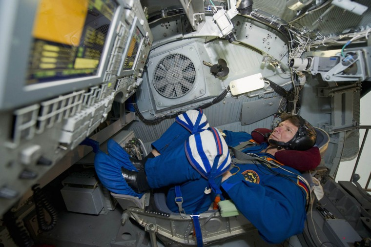 Russian cosmonaut Gennady Padalka lies inside a centrifugal machine before a training session at the Star City space center outside Moscow on March 26, 2012. (REUTERS/Sergei Remezov)