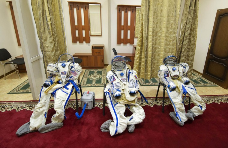 Spacesuits are seen laid out for U.S. astronaut Thomas Marshburn, Canadian astronaut Chris Hadfield and Russian cosmonaut Roman Romanenko before an exam on a simulator of the International Space Station at the Russian cosmonaut training center at Star City outside Moscow on November 28, 2012. (REUTERS/Sergei Remezov)