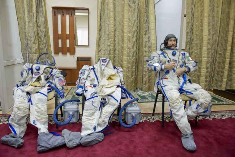 European Space Agency astronaut Luca Parmitano adjusts his space suit before taking part in a simulation exercise at the Star City cosmonaut training center outside Moscow on April 26, 2013. (REUTERS/Sergei Remezov)