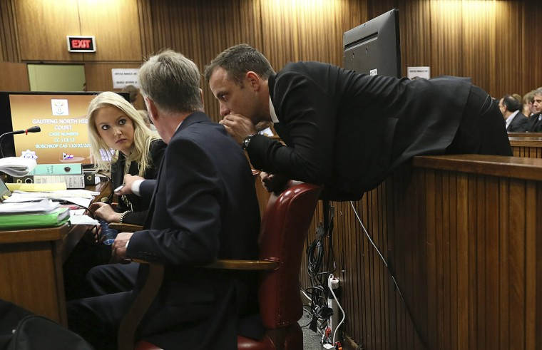 Olympic and Paralympic track star Oscar Pistorius speaks to members of his legal team on the third day of his trial for the murder of his girlfriend Reeva Steenkamp at the North Gauteng High Court in Pretoria. (Alon Skuy/Reuters)