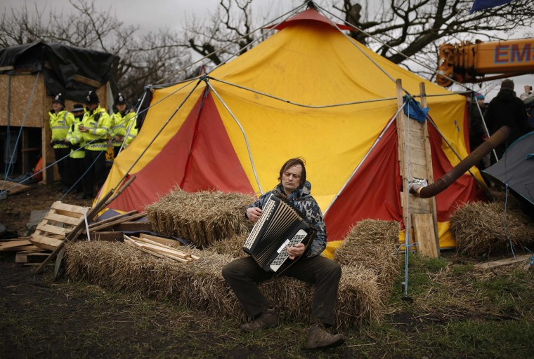 A man plays the accordion as he sits outside a tent in a protest camp set up close to the entrance of the IGas exploratory gas drilling site at Barton Moss, near Manchester, northern England, March 6, 2014. Britain may be a prime location for shale gas exploration in Europe, but a lack of onshore drilling infrastructure and local opposition will impede development, experts and geologists said at a shale conference in London. (REUTERS/Phil Noble)