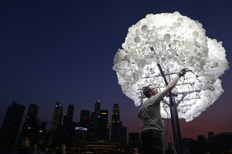 "Wayne Garrett of Canada makes final touches to his art installation ""CLOUD"" ,made up of 5000 new and recycled lightbulbs, along the Marina Bay in Singapore. Garrett and compatriot Caitlind Brown are part of the 28 groups of local and international artists who are taking part in the i Light Marina Bay biennial sustainable light art festival which will run from Friday to March 30 along the Marina Bay. (Edgar Su/Reuters)"