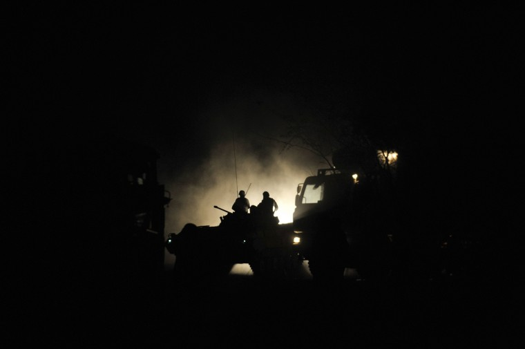 Ugandan soldiers belonging to the African Union Mission in Somalia patrol the area from a tank in the early morning hours before advancing towards the town of Qoryooley, Somalia, in this handout provided by the AU/UN Information Support Team. (Tobin Jones/AU/UN Information Support Team/via Reuters)