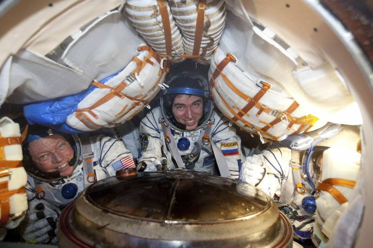 ISS crew members Michael Fossum (left), Sergey Volkov and Satoshi Furukawa sit inside the Soyuz TMA-02M capsule after landing near the town of Arkalyk, northern Kazakhstan, November 22, 2011. (REUTERS/Sergei Remezov)