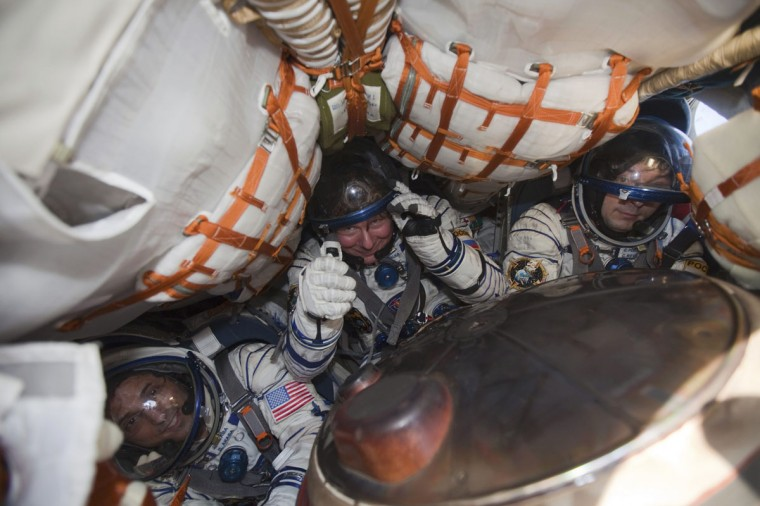 International Space Station (ISS) crew members Joseph Acaba (left), Gennady Padalka (center) and Sergei Revin sit inside the Soyuz TMA-04M capsule after landing near the town of Arkalyk in northern Kazakhstan on September 17, 2012. (REUTERS/Sergei Remezov)