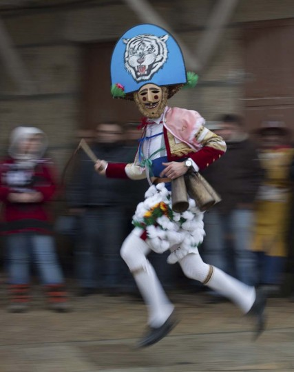 "A carnival reveller dressed as a ""Peliqueiro"" runs through a street in Spain's northwestern village of Laza March 4, 2014. ""Peliqueiros"", or ancient tax collectors, pursued villagers through the streets ringing their cowbells and hitting villagers with their sticks. (Miguel Vidal/Reuters)"