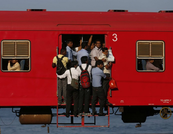 People hang onto a crowded local passenger train as they travel to Colombo March 11, 2014. (Dinuka Liyanawatte/Reuters)