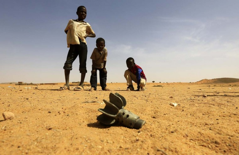 Children look at the fin of a mortar projectile that was found at the Al-Abassi camp for internally displaced persons, after an attack by rebels, in Mellit town, North Darfur March 25, 2014. (Mohamed Nureldin Abdallah/Reuters)