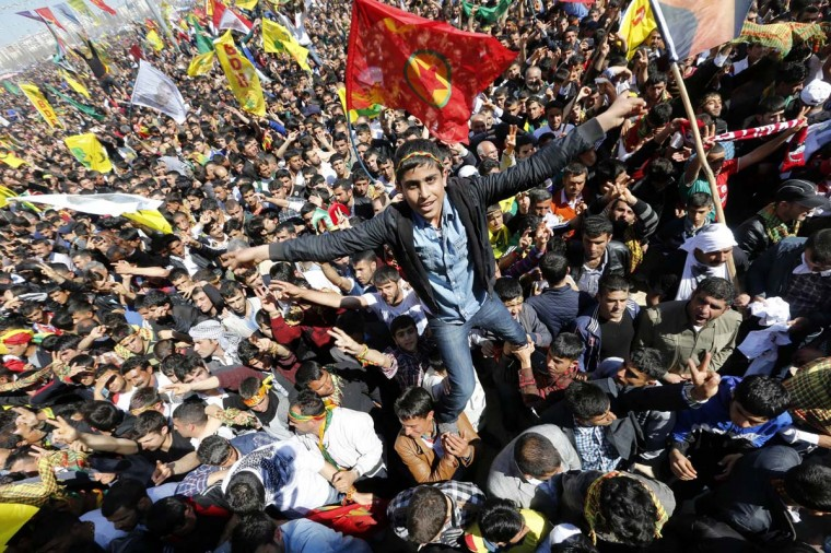 A youth gestures while being held up by others during a gathering celebrating Newroz, which marks the arrival of spring and the new year, in Diyarbakir March 21, 2014. Jailed Kurdish militant leader Abdullah Ocalan of the Kurdistan Workers Party (PKK) called on the Turkish government on Friday to create a legal framework for their peace talks, whose fate is looking increasingly uncertain a year after he called a ceasefire by his fighters. Tens of thousands gathered in Diyarbakir, the largest city in Turkey's mainly Kurdish southeast, for the Kurdish new year celebrations of Newroz, where they listened to a statement written by Ocalan in his island jail of Imrali near Istanbul. (Umit Bektas/Reuters)