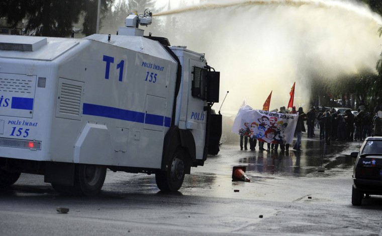"Riot police use water cannons to disperse demonstrators during an anti-government protest in the Aegean port city of Izmir, Turkey, March 16, 2014. Turkish Prime Minister Tayyip Erdogan was in Izmir to attend an election rally of his ruling AK Party. Turkey will hold municipal elections on March 30. The banner reads ""Murderer Tayyip, get out of Izmir"". (Emre Tazegul/Reuters)"