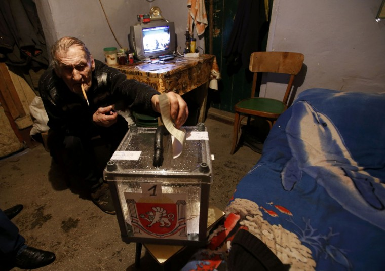 A man casts his vote in a mobile ballot box during voting in a referendum in the village of Pionerskoye outside Simferopol, Ukraine, March 16, 2014. (David Mdzinarishvili/Reuters)