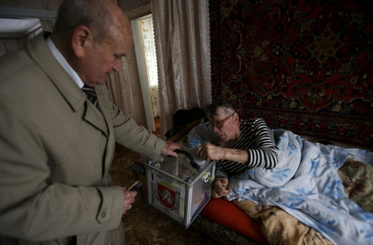 A man casts his vote from home in a mobile ballot box in a referendum in Dobroye outside Simferopol, Ukraine, March 16, 2014. (David Mdzinarishvili/Reuters)