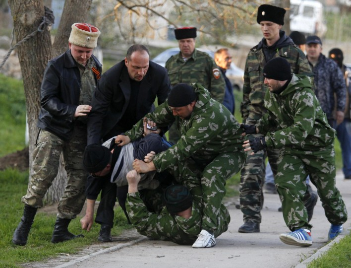 Members of a pro-Russian self-defense unit chase and detain an unidentified man outside a military airbase in the Crimean town of Belbek near Sevastopol. Russian troops forced their way into a Ukrainian airbase in Crimea with armored vehicles, automatic gunfire and stun grenades on, injuring a Ukrainian serviceman and detaining the base's commander. (Vasily Fedosenko/Reuters)