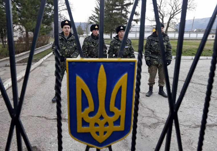 Ukrainian servicemen stand guard on the territory of a military unit in the village of Perevalnoye outside Simferopol, March 2, 2014. Ukraine mobilized for war on Sunday, after Russian President Vladimir Putin declared he had the right to invade, creating the biggest confrontation between Moscow and the West since the Cold War. (Vasily Fedosenko/Reuters)
