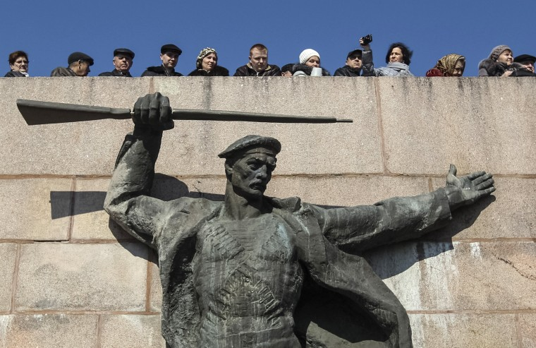 People enjoy the sunshine near a monument of the Soviet Navy in Kherson, Ukraine's region adjacent to Crimea March 13, 2014. Ahead of a referendum on Sunday when this Ukrainian region votes to decide whether to come under Moscow's rule, thousands of masked Russian troops have fanned out across the Crimea peninsula. (REUTERS/Valentyn Ogirenko)
