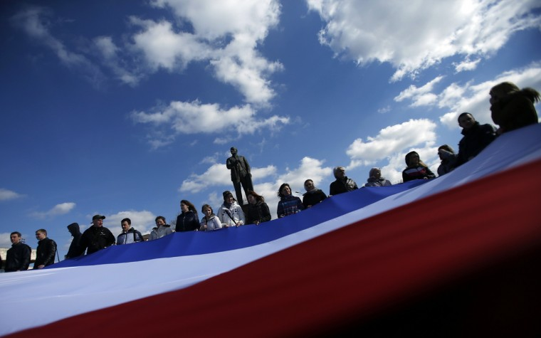 People hold a Crimean flag in front of Lenin's statue in the centre of Simferopol March 18, 2014. Russian President Vladimir Putin, defying Ukrainian protests and Western sanctions, on Tuesday signed a treaty making Crimea part Russia but said he did not plan to seize any other regions of Ukraine. (David Mdzinarishvili/Reuters)