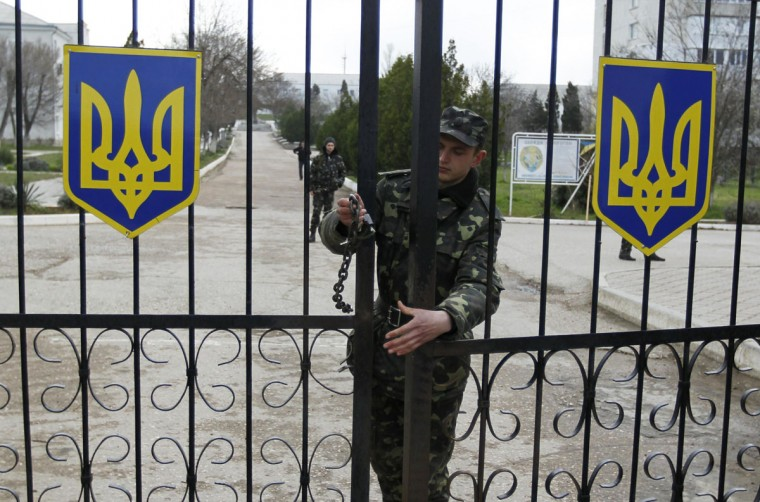 "A Ukrainian soldier closes an entrance gate at the airforce base in the Crimean town of Belbek March 20, 2014. The United States warned Moscow it was on a ""dark path"" to isolation on Wednesday as Russian troops seized two Ukrainian naval bases, including a headquarters in the Crimean port of Sevastopol where they raised their flag. (REUTERS/Shamil Zhumatov)"