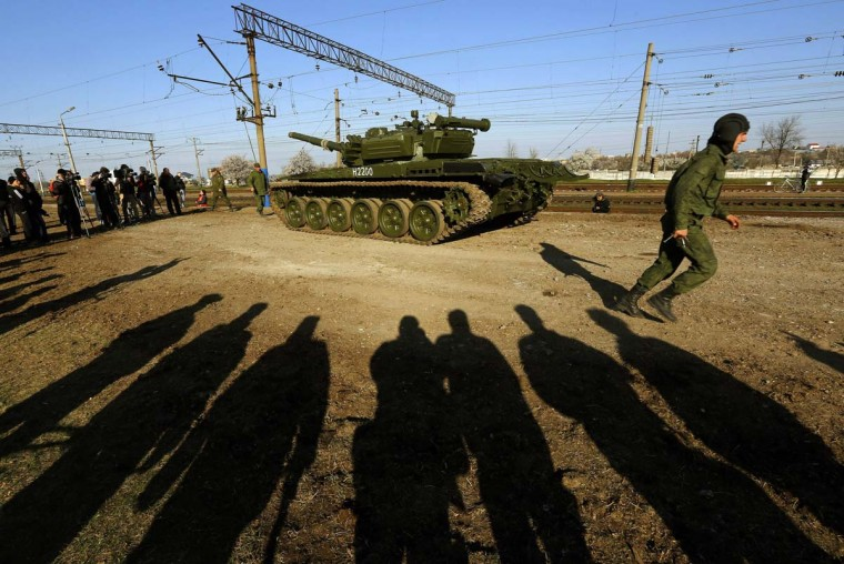 A Russian tank crew member runs in front of his T-72B tank after their arrival in Crimea in the settlement of Gvardeiskoye near the Crimean city of Simferopol March 31, 2014. Russia is withdrawing a motorized infantry battalion from a region near Ukraine's eastern border, the Russian Defence Ministry was quoted as saying by state news agencies on Monday. (Yannis Behrakis/Reuters)