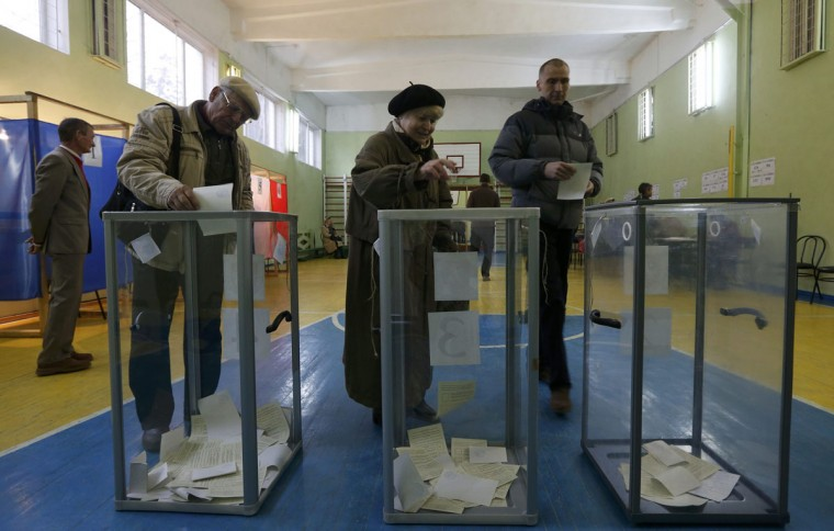 People cast their ballots during voting in a referendum at a polling station in Simferopol, Ukraine, March 16, 2014. Voting got underway in Crimea on Sunday as the inhabitants of this Ukrainian region began to cast their ballots in a referendum aimed at deciding whether the peninsula leaves Ukraine and becomes part of Russia. (Vasily Fedosenko/Reuters)