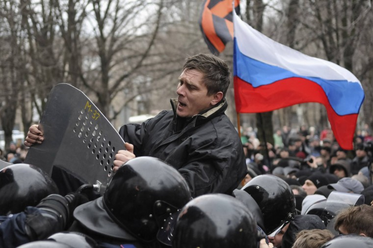"""A pro-Russian demonstrator scuffles with police during a rally in Donetsk, Ukraine, March 16, 2014. Ukraine accused """"Kremlin agents"""" on Saturday of fomenting deadly violence in Russian-speaking cities and urged people not to rise to provocations its new leaders fear Moscow may use to justify a further invasion after its takeover of Crimea. (Mikhail Maslovsky/Reuters)"""