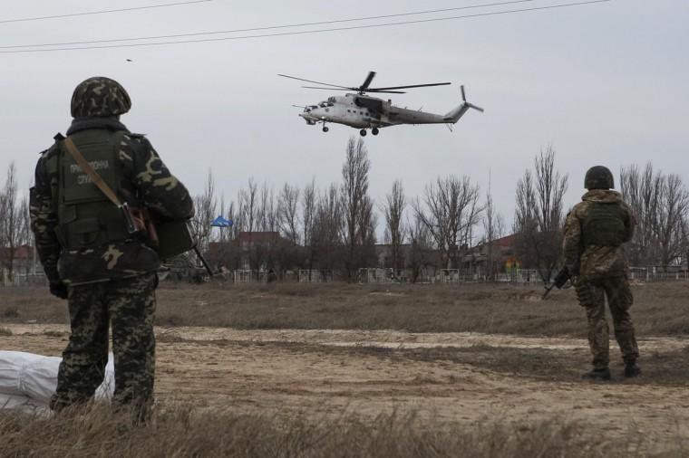 Ukrainian servicemen guard a checkpoint as a Ukrainian MI-24 military helicopter flies near the village of Strelkovo in Kherson region adjacent to Crimea, March 16, 2014. (Valentyn Ogirenko/Reuters)