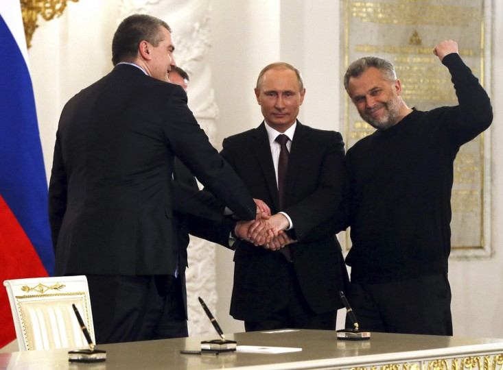 Russian President Vladimir Putin (2nd R), Crimea's Prime Minister Sergei Aksyonov (front L), Crimean parliamentary speaker Vladimir Konstantinov (back L) and Sevastopol Mayor Alexei Chaliy shake hands after a signing ceremony at the Kremlin in Moscow March 18, 2014. Putin and two Crimean leaders signed a treaty on Tuesday on making the Ukrainian Black Sea peninsula a part of Russia. The signing in the Kremlin came two days after Crimeans voted overwhelmingly to secede from Ukraine and join Russia in a referendum condemned by the Ukrainian government, the United States and the European Union as illegitimate. (Sergei Ilnitsky/Pool/Reuters)