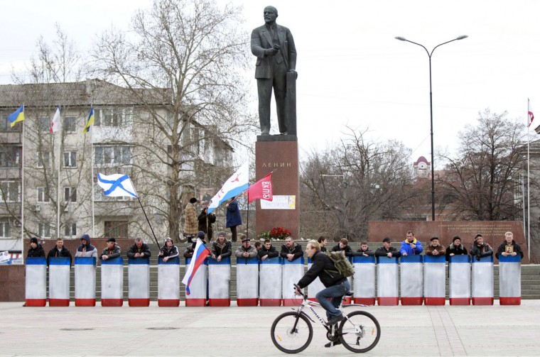 A man rides a bicycle in front of a statue of Soviet state founder Vladimir Lenin, guarded by people with shields in the Crimean city of Simferopol, March 2, 2014. (David Mdzinarishvili/Reuters)