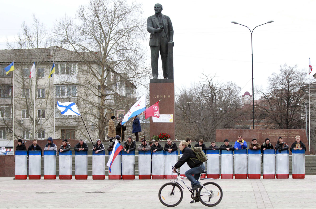 a man rides a bicycle in front of a statue of soviet state founder a man rides a bicycle in front of a statue of soviet state founder vladimir lenin guarded by people shields in the crimean city of simferopol