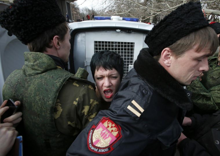 Members of Crimean self-defence units block a topless activist from the Ukrainian feminist group Femen, who is taking part in an anti-war protest near the Crimean parliament building in Simferopol, March 6, 2014. European Union leaders were set to warn but not sanction Russia on Thursday over its military intervention in Ukraine after Moscow rebuffed Western diplomatic efforts to persuade it to pull forces in Crimea back to their bases. (REUTERS/David Mdzinarishvili)