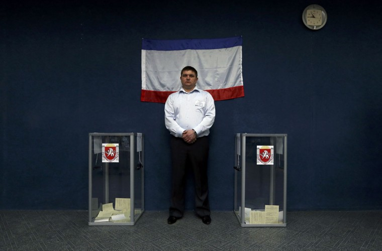 An official waits for voters during the referendum on the status of Ukraine's Crimea region at a polling station in a predominantly Tatar district of the town of Bakhchisaray, Ukraine, March 16, 2014. (Sergei Karpukhin/Reuters)