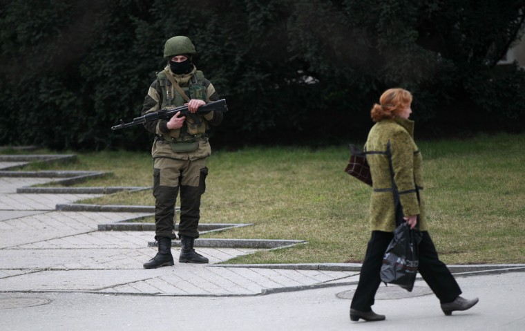 A woman walks past an armed man near the regional parliament building in the Crimean city of Simferopol March 2, 2014.(David Mdzinarishvili/Reuters)