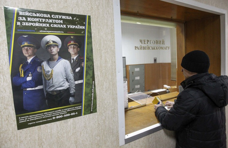 A man stands in front of a counter's window at a district army recruiting office in Kiev March 2, 2014. Ukraine mobilized its troops on Sunday. (Valentyn Ogirenko/Reuters)