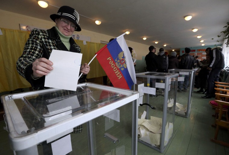 A woman holds a Russian flag as she casts her ballot during the referendum on the status of Ukraine's Crimea region at a polling station in Bakhchisaray, March 16, 2014. Crimeans decided on Sunday whether to break away from Ukraine and join Russia in a referendum that has alarmed the ex-Soviet republic and triggered the worst crisis in East-West relations since the Cold War. (Sergei Karpukhin/Reuters)