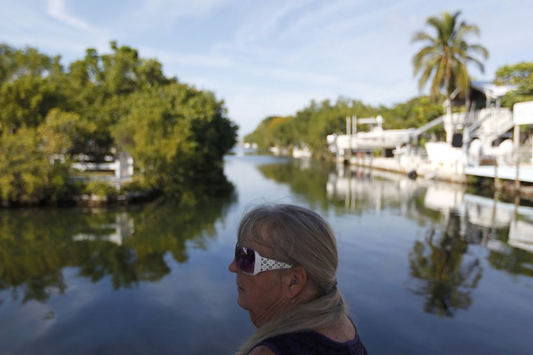 Everlyn Varrieur sits on the dock of her home, next to her son Doug Varrieur who set up a practice firing range in the yard of his home in Big Pine Key in the Florida Keys March 5, 2014. The mother acts as a safety officer for the son, watching for boats and people who might happen to pass behind the backstop to the firing range. Varrieur, 57, discovered a little-noticed part of Florida law which prohibits local governments from restricting gun rights in any way, and in December he set up a personal gun range on his property in a residential subdivision. Neighbors were outraged by the live gunfire, but their surprise was nothing compared to that of municipal leaders, who were shocked to realize there was nothing they could do about it. Picture taken March 5, 2014. (REUTERS/Andrew Innerarity)