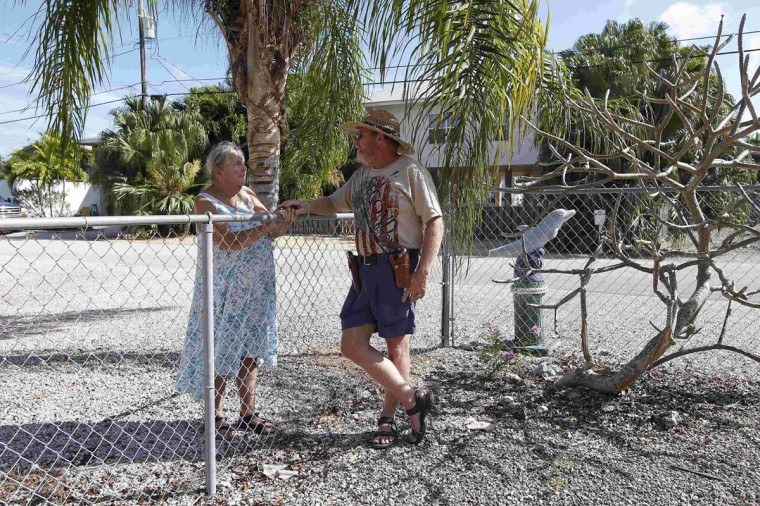 Everlyn Varrieur (L) chats from her yard, across the fence with her son Doug Varrieur (R) who set up a practice firing range in the yard of his home in Big Pine Key in the Florida Keys March 5, 2014. Varrieur, 57, discovered a little-noticed part of Florida law which prohibits local governments from restricting gun rights in any way, and in December he set up a personal gun range on his property in a residential subdivision. Neighbors were outraged by the live gunfire, but their surprise was nothing compared to that of municipal leaders, who were shocked to realize there was nothing they could do about it. Picture taken March 5, 2014. (REUTERS/Andrew Innerarity)