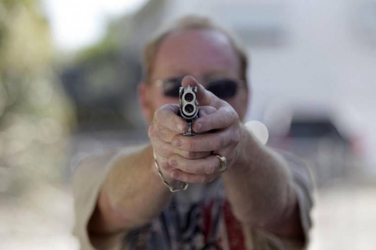 Doug Varrieur practices his firing stance on the firing range with an unloaded weapon in the yard of his home in Big Pine Keys in the Florida Keys March 5, 2014. Varrieur, 57, discovered a little-noticed part of Florida law which prohibits local governments from restricting gun rights in any way, and in December he set up a personal gun range on his property in a residential subdivision. Neighbors were outraged by the live gunfire, but their surprise was nothing compared to that of municipal leaders, who were shocked to realize there was nothing they could do about it. Picture taken March 5, 2014. (REUTERS/Andrew Innerarity)
