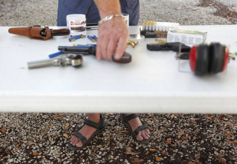 Doug Varrieur handles a handgun on a table at the firing range in the yard of his home in Big Pine Key in the Florida Keys March 5, 2014. Varrieur, 57, discovered a little-noticed part of Florida law which prohibits local governments from restricting gun rights in any way, and in December he set up a personal gun range on his property in a residential subdivision. Neighbors were outraged by the live gunfire, but their surprise was nothing compared to that of municipal leaders, who were shocked to realize there was nothing they could do about it. Picture taken March 5, 2014. (REUTERS/Andrew Innerarity)