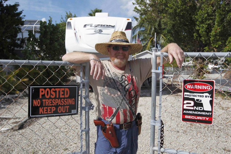 Wearing two revolvers, Doug Varrieur poses at a gate to his home in Big Pine Key in the Florida Keys March 5, 2014. Varrieur, 57, discovered a little-noticed part of Florida law which prohibits local governments from restricting gun rights in any way, and in December he set up a personal gun range on his property in a residential subdivision. Neighbors were outraged by the live gunfire, but their surprise was nothing compared to that of municipal leaders, who were shocked to realize there was nothing they could do about it. Picture taken March 5, 2014. (REUTERS/Andrew Innerarity)