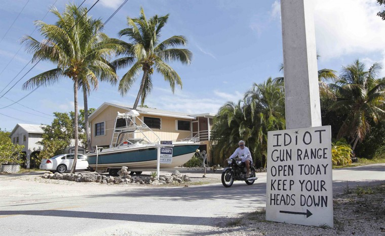 A sign placed by a neighbor is seen at the intersection closest to the home of Doug Varrieur in Big Pine Key in the Florida Keys March 5, 2014. Varrieur, 57, discovered a little-noticed part of Florida law which prohibits local governments from restricting gun rights in any way, and in December he set up a personal gun range on his property in a residential subdivision. Neighbors were outraged by the live gunfire, but their surprise was nothing compared to that of municipal leaders, who were shocked to realize there was nothing they could do about it. Picture taken March 5, 2014. (REUTERS/Andrew Innerarity)